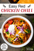 "Bowl of chili topped with sour cream, red onion, cilantro, and grated cheddar cheese. Text overlay says: ""Easy Red Chicken Chili (with soaked beans for gentle digestion!)"""