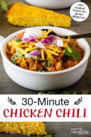 "Bowl of chili topped with sour cream, red onion, cilantro, and grated cheddar cheese, with a slice of cornbread in the background. Text overlay says: ""30-Minute Chicken Chili (with soaked beans for gentle digestion!)"""