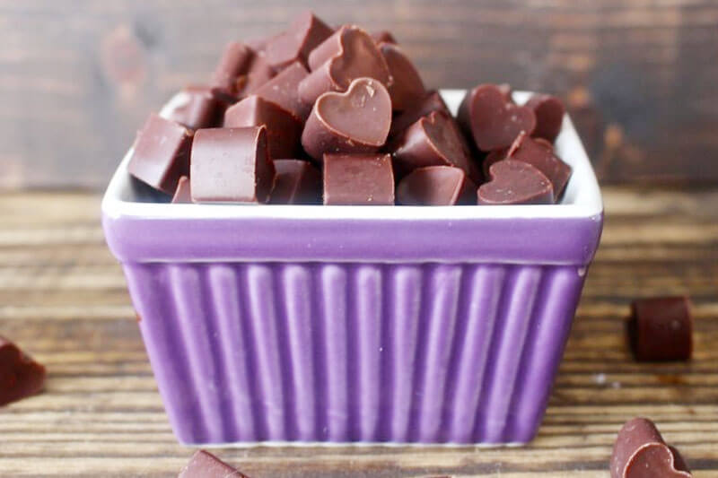 Homemade heart-shaped chocolate chunks in a purple ceramic dish.
