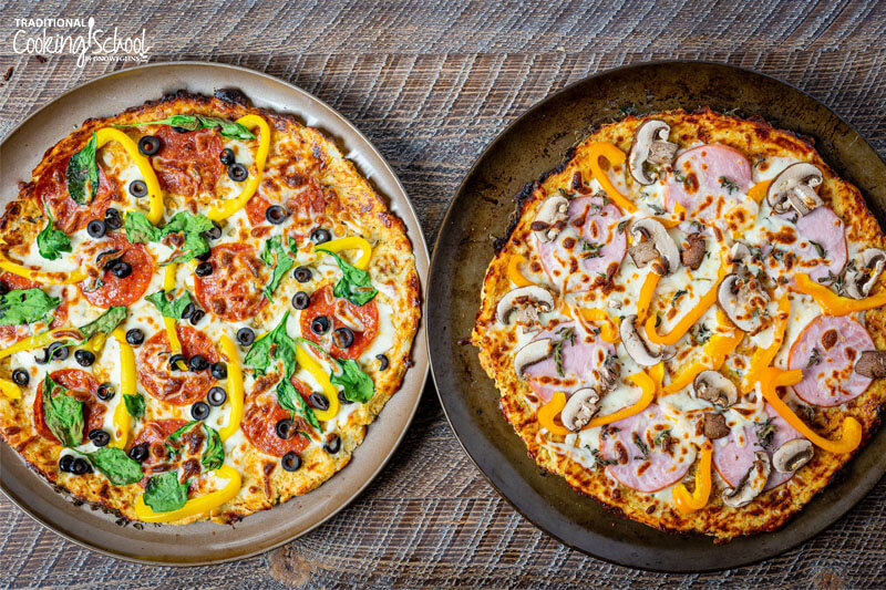 Two crispy, golden brown cauliflower pizzas on baking trays topped with veggies, cheese, and meats.