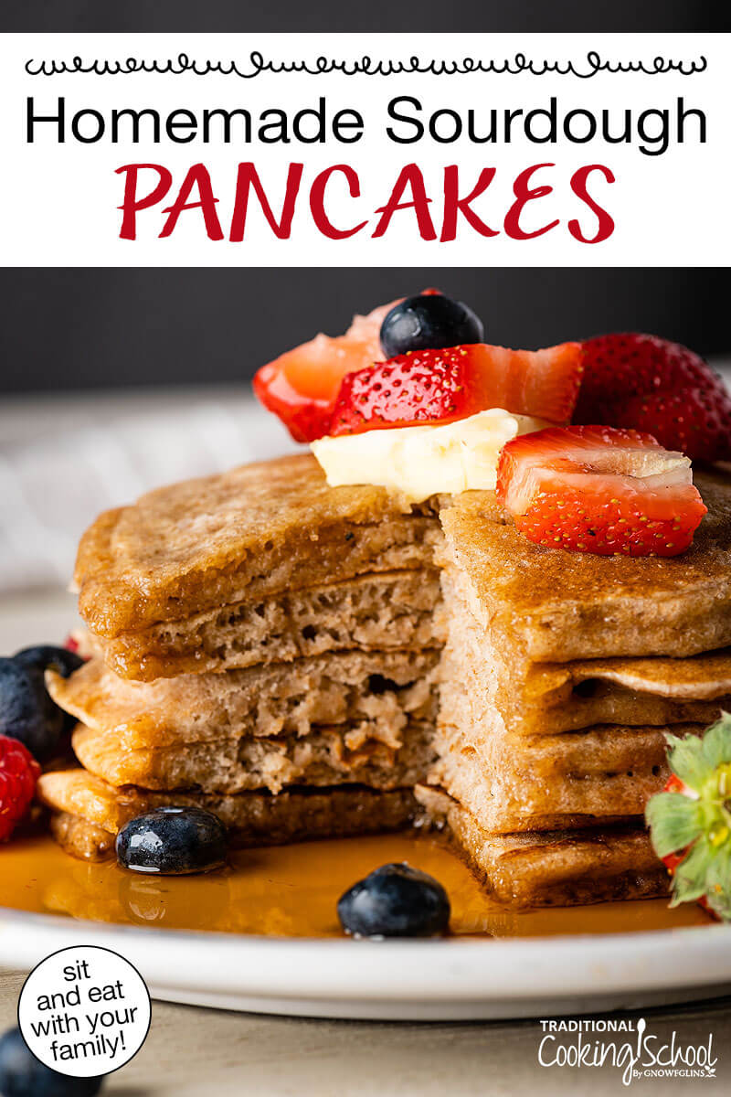 "Stack of pancakes topped with fresh fruit and drizzled with maple syrup. Text overlay says: ""Homemade Sourdough Pancakes (sit and eat with your family!)"""