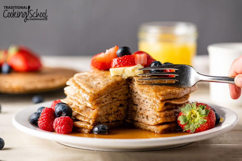 Stack of sourdough pancakes on a plate topped with fresh fruit, butter, and syrup, with a fork poised to take a bite.