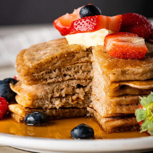 Stack of sourdough pancakes on a plate topped with fresh fruit, butter, and syrup.