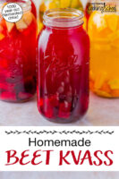 """Ruby-colored beet kvass in a half gallon jar. Text overlay says: """"Homemade Beet Kvass (1000 year old fermented drink!)"""""""
