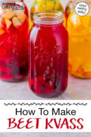 """Beet kvass in half gallon jars, some flavored with citrus and other fruits. Text overlay says: """"How To Make Beet Kvass (bold earthy salty!)"""""""