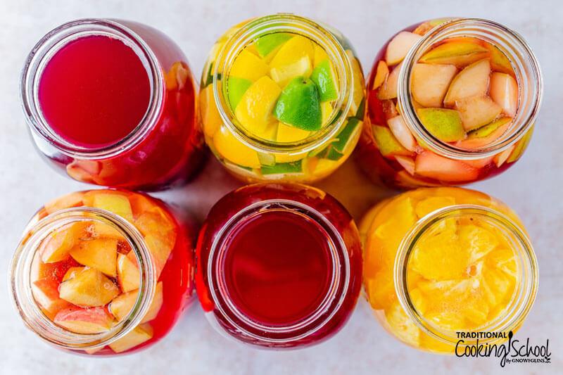 Jars of flavored and plain beet kvass, including lemon-lime, ginger-pear, ginger-orange-carrot, and apple-cinnamon.