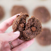 Close-up shot of a double chocolate chip cookie broken in two to show the soft texture.