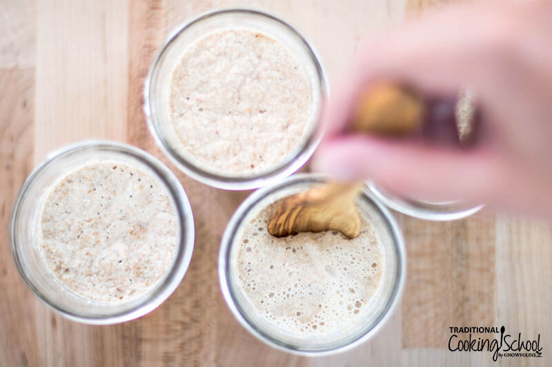 Woman's hand stirring bubbly sourdough starter in a small glass jar.
