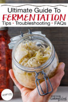 """Person's hand holding up an open jar of homemade sauerkraut. Text overlay says: """"Ultimate Guide to Fermentation: Tips, Troubleshooting, FAQs (KYF172)"""""""