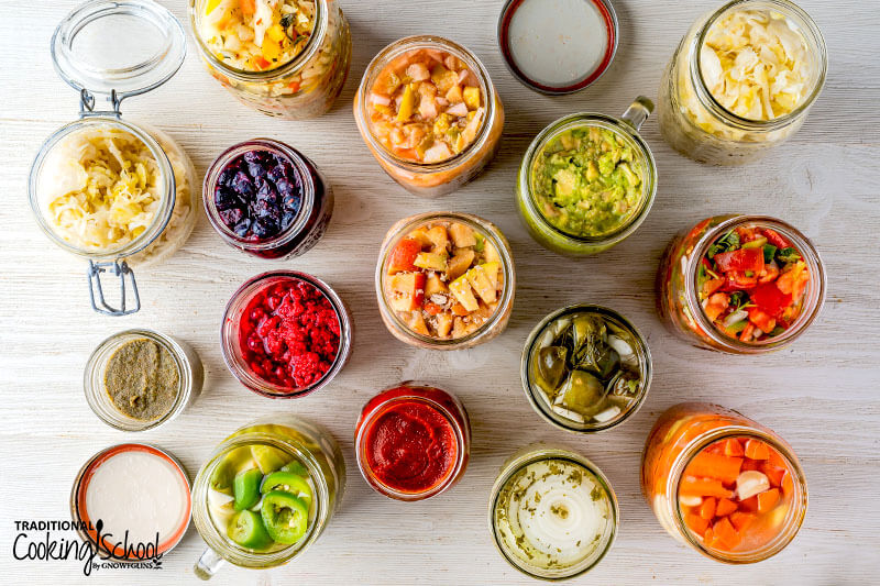 Overhead shot of a wide variety of different colorful ferments in open jars.
